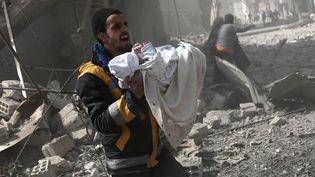 Un Syrien sauve un enfant des ruines d'un immeuble, dans la région de la Ghouta en Syrie, le 13 février 2018. (AFP)