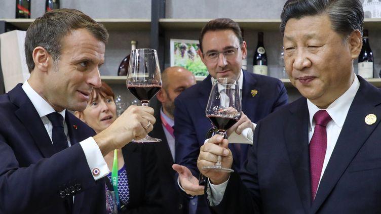 Les présidents chinois Xi Jinping (D) et français Emmanuel Macron (G) dégustent du vin sur le pavillon français de la foire aux exportations de Shanghai (Chine), le 5 novembre 2019. (LUDOVIC MARIN / AFP)