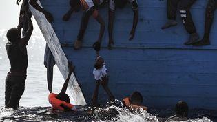 Des migrants essaient de sauver un enfant avant d'être eux-mêmes secourus par l'ONG Proactiva Open Arms, le 4 octobre 2016 enMéditerrannée, au largedes côteslibyennes. (ARIS MESSINIS / AFP)
