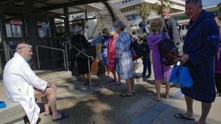 Des détenteurs du passeport vert attendent de rentrer dans un centre aquatique de Tel Aviv. (GIL COHEN-MAGEN / AFP)