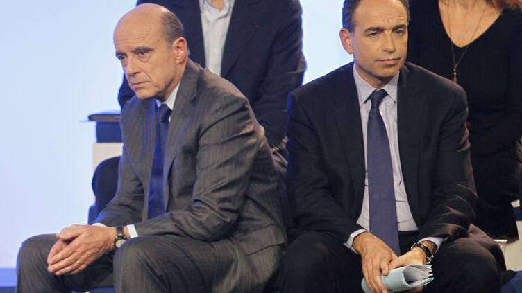 Le ministre des Affaires étrangères, Alain Juppé (à g.), et le secrétaire général de l'UMP, Jean-François Copé, lors de la troisième convention de l'UMP, le 6 décembre à Paris. (CHARLES PLATIAU / REUTERS)