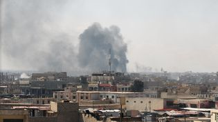 De la fumée s'échappe depuis un secteur de Mossoul (Irak), samedi 25 mars 2017, après une frappe aérienne menée en appui de troupes engagées contre le groupe Etat islamique. (AHMAD AL-RUBAYE / AFP)