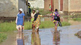 Des femmes marchent dans l'eau, au nord-ouest de Bujumbura, au Burundi, après des pluies torrentielles qui ont détruit une centaine de maisons en mars 2017. (STRINGER / AFP)
