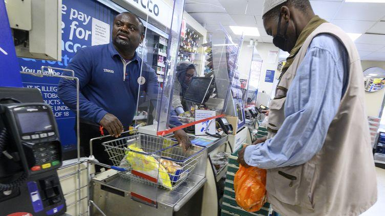 Un caissier dans un supermarché Tesco à Londres, le 5 mai 2020. (JUSTIN TALLIS / AFP)