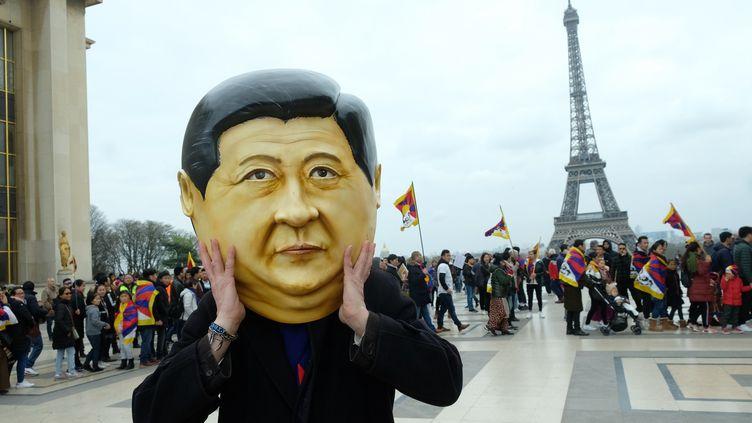 Une personne porte un masque à l'effigie de Xi Jinping, lors d'une manifestation de Tibétains sur l'esplanade du Trocadéro à Paris, le 24 mars 2019. (NATHANAEL CHARBONNIER / RADIO FRANCE)