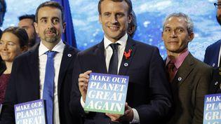 """Le président de la République, Emmanuel Macron, brandit un panneau """"Make our planet great again"""", le 11 décembre 2017 à Paris. (PHILIPPE WOJAZER / AFP)"""
