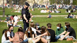 Un policier contrôle des passants, le 31 mars 2021 à Paris. (BERTRAND GUAY / AFP)