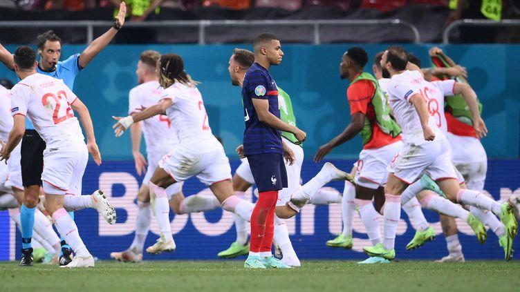 Après son tir au but manqué, la solitude de Kylian Mbappé contraste avec l'immense joie des Suisses, qualifiés pour la première fois de leur histoire en quarts de finale d'un Euro. (FRANCK FIFE / AFP)