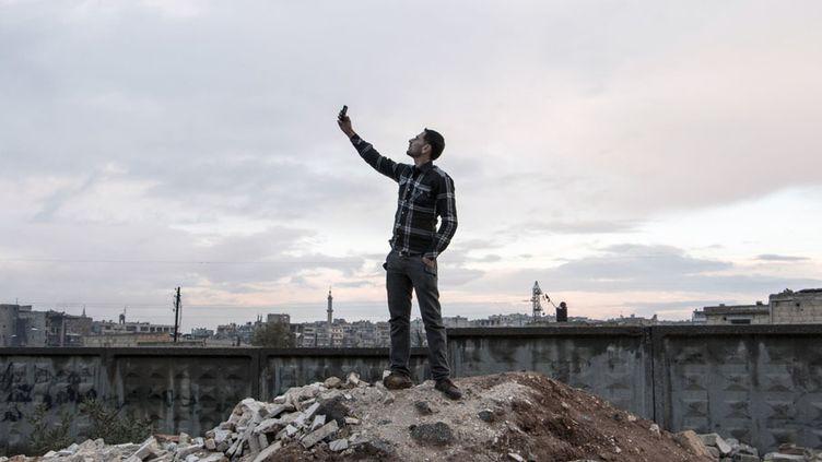 Un homme tente de capter du réseau téléphonique à Alep (Syrie), le 26 novembre 2014. (KARAM AL-MASRI / AFP)