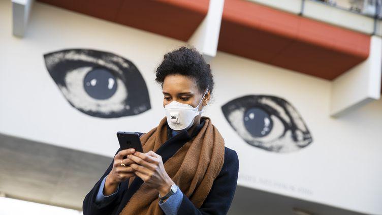 Une femme consulte son smartphone, le 1er avril 2020, à Berlin (Allemagne). (EMMANUELE CONTINI / NURPHOTO / AFP)