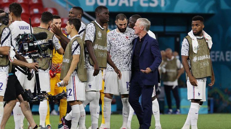Le footballeur français Karim Benzema entouré de Didier Deschamps lors du match de l'Euro 2021 contre le Portugal, le 23 juin 2021, à Budapest (Hongrie). (BERNADETT SZABO / POOL / AFP)