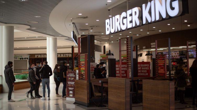 Des personnes font la queue devant une enseigne Burger King, au centre commercial de Saint-Herblain (Loire-Atlantique), le 13 janvier 2021. (LOIC VENANCE / AFP)