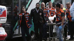 Des secouristes israéliens transportent un corps sur une civière le 13 octobre 2015, à Jérusalem-Est, après une attaque contre un bus. (GALI TIBBON / AFP)
