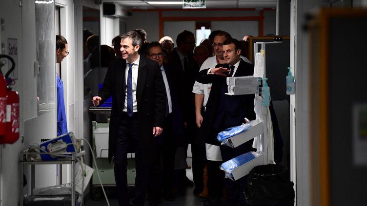 Olivier Véran et Emmanuel Macron rendent visite à des soignants, le 27 février 2020, à la Pitié-Salpêtrière, à Paris. (MARTIN BUREAU / AFP)