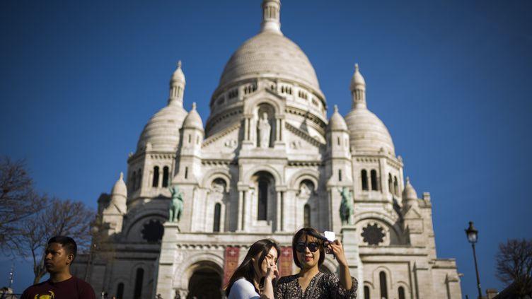 Des touristes prennent un selfie devant le Sacré-Cœur, à Paris, le 30 mars 2017. (Photo d'illustration) (LIONEL BONAVENTURE / AFP)