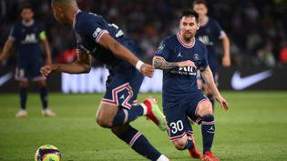 Lionel Messi sert Kylian Mbappé lors du match entre le PSG et l'OL, le 19 septembre (FRANCK FIFE / AFP)
