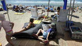 Des enfants lisent sur la plage, à Biscarrosse (Landes), 2010 (JEAN-PIERRE MULLER / AFP)