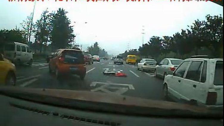 Capture d'écran d'une vidéo mise en ligne sur le site Youku. On y voit une voiture contournant le corps d'une femme qui vient de se jeter d'un pont, près de Chengdu (Chine), le 2 novembre 2011. (FTVi)