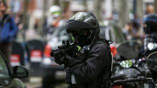 """Un policier vise avec un lanceur de balle de défense, le 11 mai 2019 à Toulouse, lors d'une manifestation de """"gilets jaunes"""". (FREDERIC SCHEIBER / HANS LUCAS / AFP)"""