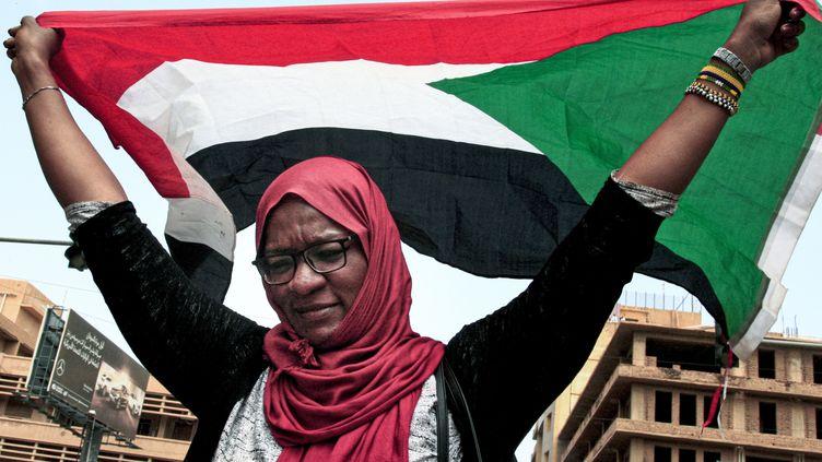 Une femme brandit le drapeau soudanais durant le soulèvement populaire contre le président Omar el-Béchir, le 12 septembre 2019 à Khartoum. (EBRAHIM HAMID / AFP)
