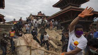 Un Népalais tentant de dégager les ruines d'un temple, jeudi 30 avril à Katmandou (Népal), où un séismea partiellement détruit la ville. (PALANI MOHAN / IFRC / AFP)