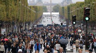 Des piétons sur les Champs-Elysées lors d'une journée sans voiture, le 1er octobre 2017 à Paris. (ZAKARIA ABDELKAFI / AFP)