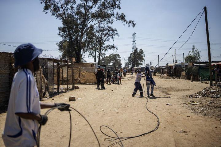 Démontage d'un réseau électrique sauvage dans un quartier de Johannesburg par des employés d'Eskom, le 29 septembre 2020. (MICHELE SPATARI / AFP)