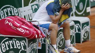 Malmené par l'Allemand Tommy Haas, le russeenfouit sa tête sous sa serviette après avoir cassé sa raquette, le 3 juin 2013 à Roland-Garros. (PATRICK KOVARIK / AFP)