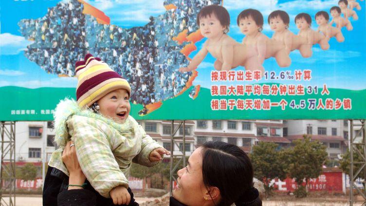 Une Chinoise et son bébé devant une affichevantant la politique de l'enfant unique, le 1er février 2005 àShaoyang, dans le Hunan (Chine). (LV JIANSHE / IMAGINECHINA)