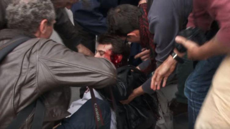 Un homme blessé à la tête lors d'une manifestation à Paris est secouru par plusieurs personnes, le 26 mai 2016. (LDC NEWS YOUTUBE / YOUTUBE)