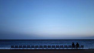 Deux personnes sont assises sur la Promenade des Anglais à Nice, le 21 février 2021. Photo d'illustration. (VALERY HACHE / AFP)