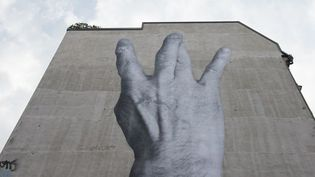 """Un mur de Berlin signé du """"photograffeur"""" JR.  (John MacDougall / AFP)"""