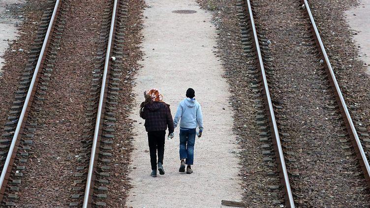 Deux migrants sur le site d'Eurotunnels à Coquelles (Pas-de-Calais), le 29 juillet 2015. (MAXPPP)