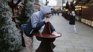 Un marchand prépare, jeudi 22 novembre 2016, la réouverture du marché de Berlin (Allemagne), touché par l'attaque au camion-bélier. (HANNIBAL HANSCHKE / REUTERS)