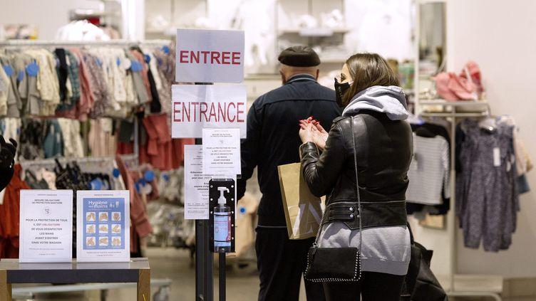 Une femme à l'entrée d'un magasin qui se désinfecte les mains, le 11 mai 2020. (GUILLAUME BONNEFONT / MAXPPP)