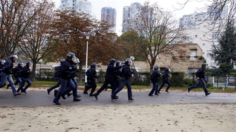 Des policiers en train de courir durant les incidents du 19 octobre à Nanterre (Hauts-de-Seine). (AFP - THOMAS SAMSON)