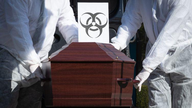 Employés de pompes funèbres transportantle cercueil d'une personne morte du coronavirus (image d'illustration). (BENOIT DOPPAGNE / MAXPPP)