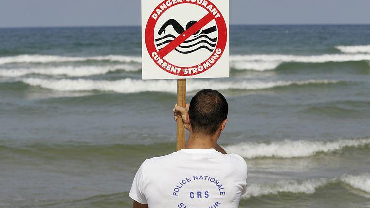 Un maître-nageur installe un panneau mettant en garde contre des baïnes à Lacanau (Gironde), le 21 juillet 2004. (PATRICK BERNARD / AFP)