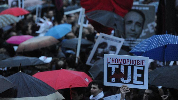 """Manifestants sous des parapluies tenant des pancartes avec slogan """"l'homophobie tue"""", en avril 2013. (NATHANAEL CHARBONNIER / FRANCE-INFO)"""
