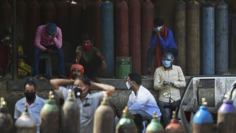 Plusieurs personnes attendent pour remplir desbouteilles d'oxygènes, nécessaires à la prise en charge des patients hospitalisés pour le Covid-19, àAllahabad (Inde), le 24 avril 2021. (SANJAY KANOJIA / AFP)