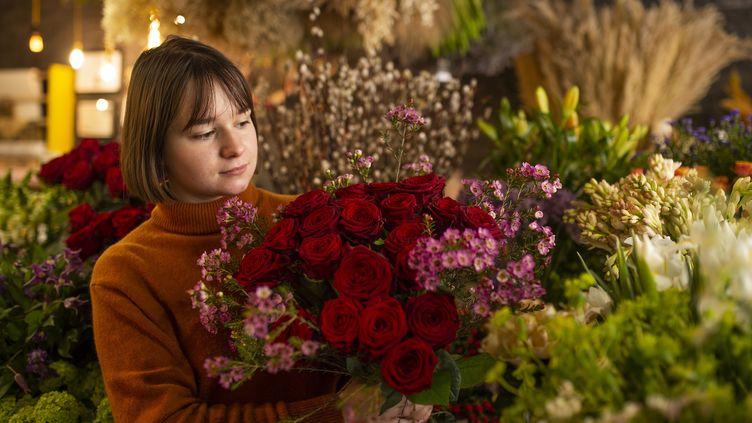 Une fleuriste tient un bouquet de roses rouges, le 11 février 2021, à Nantes. (MAXPPP)