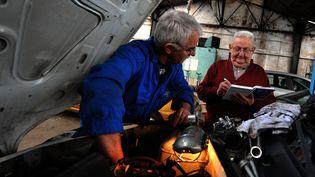 Des seniors travaillent dans un garage automobile. (MYCHELE DANIAU / AFP)