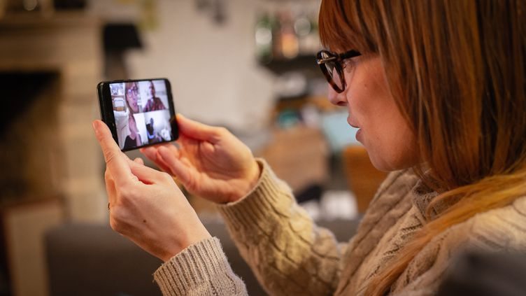 Une femme parle avec des amis via une application de téléconférence, le 29 mars 2020, à Angers (Maine-et-Loire). (THIBAUD VAERMAN / HANS LUCAS)