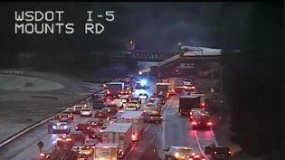 Une image de vidéosurveillance publiée par le département des Transports de l'Etat de Washington montre letrainqui a déraillé au-dessus d'une autoroute,le 18 décembre 2017. (ERIC BARADAT / WSDOT / AFP)
