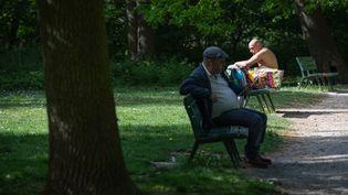 Deux promeneurs apprécient le beau temps au bois de Vincennes à Paris, le 17 avril 2020. (THOMAS CYTRYNOWICZ / AFP)