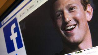 Une image d'illustration montrant une page de la version anglaise de Facebook, avec le portrait du fondateur du réseau social, Mark Zuckerberg, le 22 mars 2018. (MLADEN ANTONOV / AFP)