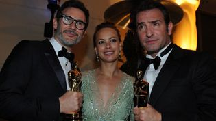 """Michel Hazanavicius, Bérénice Béjo et Jean Dujardin au 84e Oscars, en février 2012, avec les deux statuettes pour """"The Artist""""  (VALERIE MACON / AFP)"""