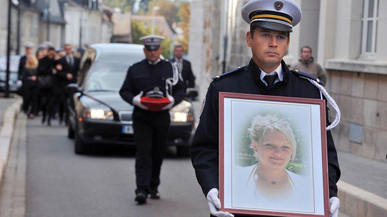 Un policier porte le portrait d'Anne Pavageau, le 20 octobre 2011 à Bourges (Cher), lors des obsèques de la policière tuée dans l'exercice de ses fonctions le 14 octobre 2011 par un forcené armé d'un sabre. (ALAIN JOCARD / AFP)