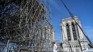Des échaffaudages et un ouvrier au sommet de la cathédrale, non loin des deux tours, le 17 juillet 2019 (STEPHANE DE SAKUTIN / AFP)