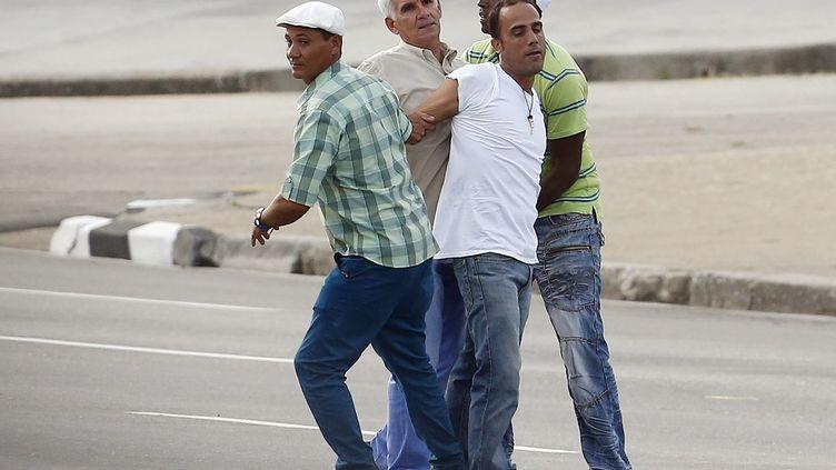 La sécurité cubaine arrête un homme (chemise blanche) qui a jeté des brochures au cours de la première messe du pape à La Havane, le 20 septembre 2015. (CARLOS GARCIA RAWLINS / REUTERS )